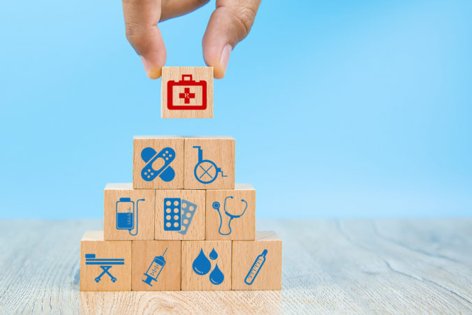 Close up hand choose Health care and medical symbols on wooden blocks toy stacked in Pyramid shape for health insurance concepts.