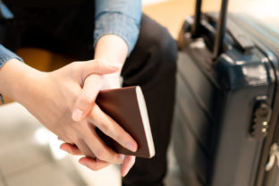 Male tourist holding passport in airport terminal