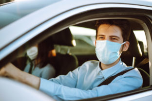 Man driving a car puts on a medical mask during an epidemic in quarantine city.