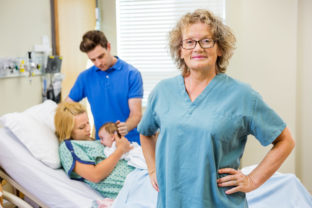 Mature Nurse Standing With Couple And Newborn Baby In Background