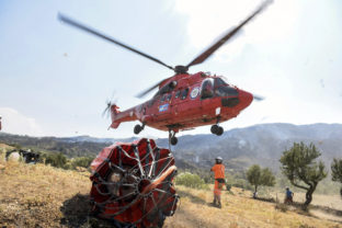A firefighting helicopter prepares to take water from a lake in Akcaova Village, near Cine, Aydin, Turkey, Saturday, Aug. 7, 2021. In Turkey's seaside province of Mugla, most fires appeared to be under control Saturday. Municipalities in Marmaris and the wider Mugla province said cooling efforts were ongoing in areas where fires were brought under control.()