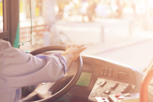 Cropped shot of bus driver holding steering whee