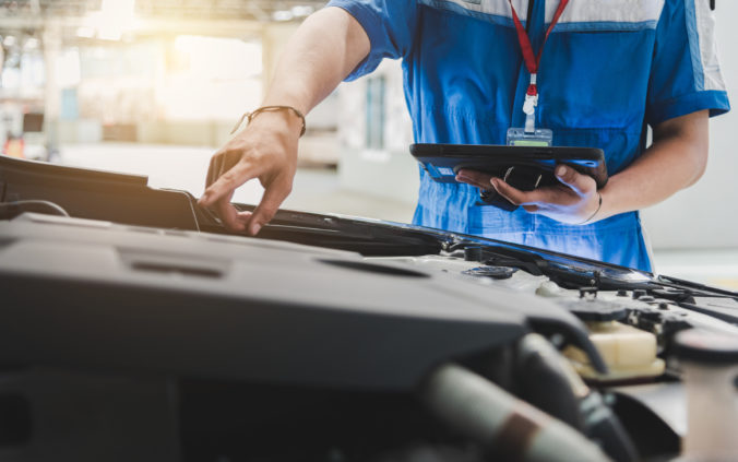 Auto mechanic uses the tablet to check.