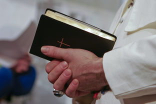 Man in popes garment holding holy bible