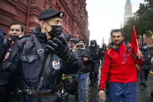 Russia Election Protest Police escort a demonstrator with a red flag during a protest against the results of the Parliamentary election near Red Square in Moscow, Russia, Saturday, Sept. 25, 2021. The Communist Party has called for a rally in Moscow on Saturday and was urged by the authorities Friday to remove the announcements from its website, otherwise it would be blocked — pressure that a party with seats in the parliament and which backs many of the Kremlin's policies has rarely faced before.