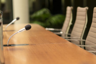 Isolated view of a microphone in the front of a conference room among blurred other mikes in the background