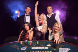 Group of a young wealthy friends are playing poker at a casino