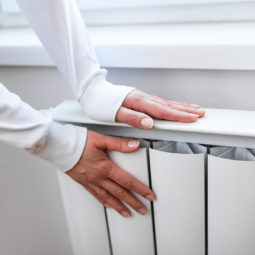 Heavy duty radiator - central heating. Woman is getting her hands warm on Home central heating system