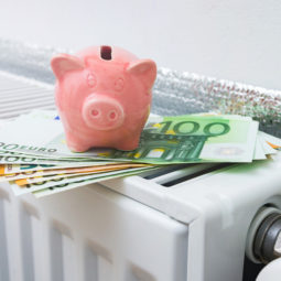 Domestic radiator heating with piggy bank on euro banknotes. Save heating costs concept image.
