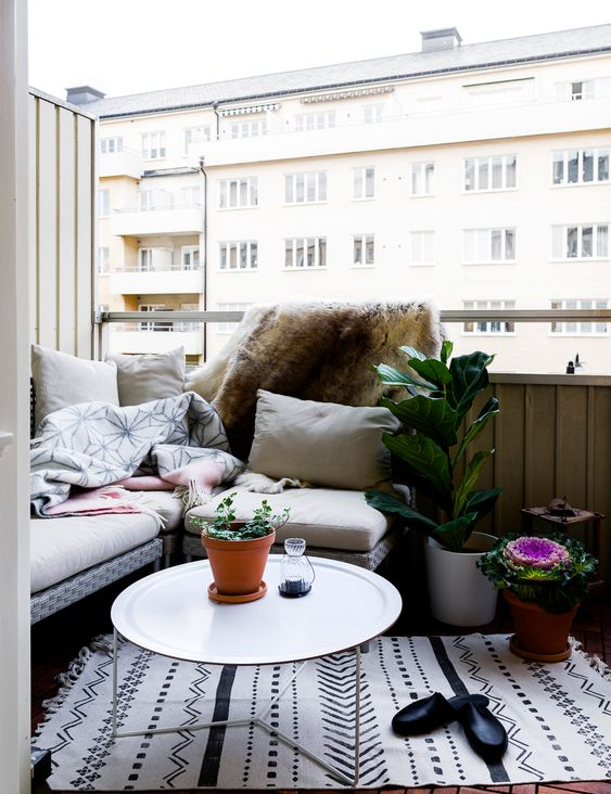 06 a welcoming nook with an l shaped bench potted plants and a small coffee table.jpg