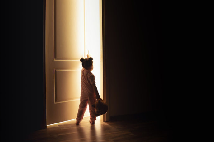 Little girl opens the door to the light in darkness