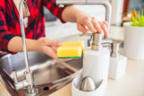 Woman is dosing the soap on the sponge in the kitchen.