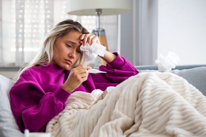 Sickness, seasonal virus problem concept. Woman being sick having flu lying on sofa looking at temperature on thermometer. Sick woman lying in bed with high fever. Cold flu and migraine.