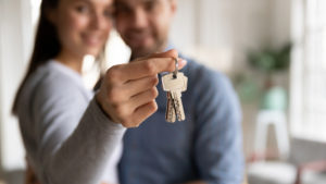 Close up happy young woman hugging man, holding keys